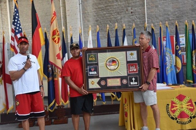 Colonel Mario Washington, commander of the Wiesbaden garrison, Mitchell Jones, assistant to the garrison commander and the garrison command sergeant.  Major Chris Truchon, show the plaque given to the command sergeant major for his farewell from the garrison.