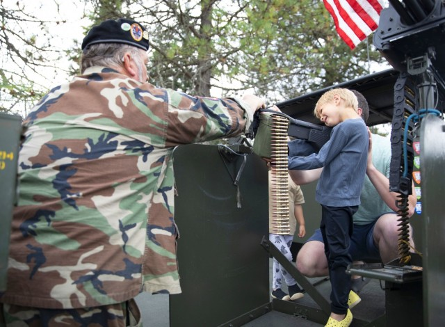 Steve Sumaral, a member of the Gamewarden of Vietnam Past to Present shows attendees the twin M2HB .50 caliber (12.7 mm) machine guns onboard a Navy Patrol Boat, River (PBR)  that was used during the Vietnam War. Sumaral is wearing a black beret, worn only by U.S. Navy's brown-water force, a force that patrolled the Mekong River Delta to transport people to medical facilities, check legal papers and to stop the flow of guns and personnel.