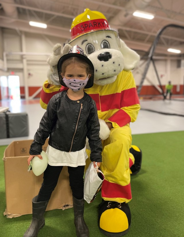 """An eager child receives a special visit from the Fort Greely Fire Department mascot """"Sparky"""" during the annual Back to School Bash August 6 at the Physical Readiness Training Facility. The Back to School Bash is an annual event that provides the Fort Greely community an opportunity to participate in family friendly activities while also preparing for the upcoming school year."""