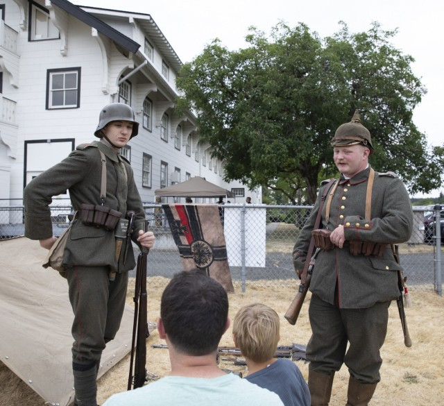 Huckleberry Hammer and Caleb Lundeen, living history historians and members of the PNW Great War speak to attendees about German military uniforms from World War I at the Lewis Army Museum living history exhibit at Joint Base Lewis-McChord, Wash., July 31, 2021.  Their uniforms depict a vast contrast between the start and the end of the war uniforms (U.S. Army photo by Spc. Nicole Nicolas).