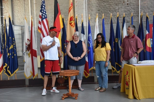 Gwyn Truchon, wife of the Wiesbaden Command Sgt.  The Major, received a special thank you gift from a hand-carved table, from the Spouses Club, as Garrison Commander, Col. Mario Washington, his wife, Elizabeth and Command Sgt.  Shift, Chris Truchon is watching.