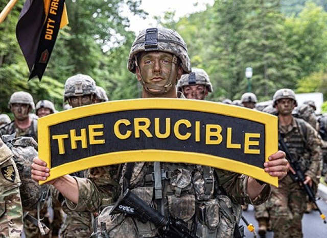 A new cadet from the U.S. Military Academy Class of 2025 carries a sign, ʻThe Crucible,' as his classmates complete the final mile of March Back Monday at West Point.
