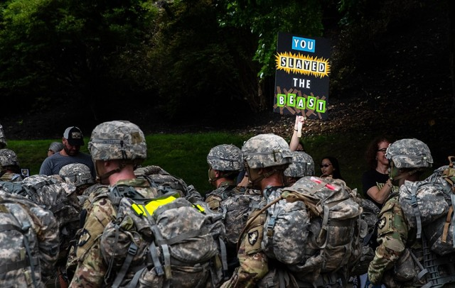 A family member of a Class of 2025 cadet holds a sign congratulating the new cadets on ʻSlaying the Beast' as they complete their initial summer training at West Point.