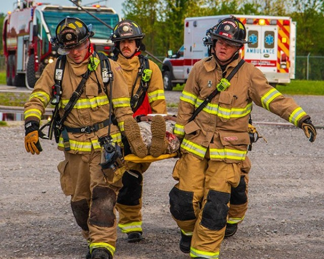 Firefighters Drew Wilson, Ryan Harrell and Jake Haynes, Fort Campbell Fire Department, use a litter to carry a wounded Soldier May 2018 during a full-scale exercise on post. The exercise was conducted to evaluate Fort Campbell's emergency service response time and procedures, the simulation included a crashed helicopter, several fires and notionally wounded personnel portrayed by Fort Campbell Soldiers. Specific details on the scenario and timeframe for this year's full-scale exercise have not been released to make sure emergency response preparedness is properly tested, but the community should experience minimal disruption.