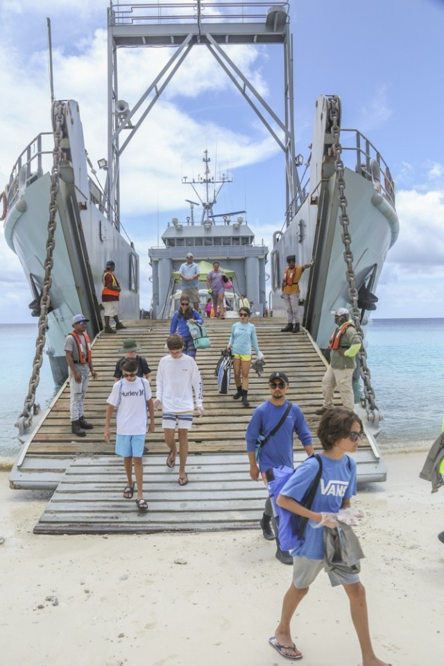 Personnel and students from U.S. Army Garrison-Kwajalein Atoll disembark from the USAV Great Bridge for the 2021 Child and Youth Services Commander's Summer Challenge beach clean-up on Bigej Aug. 1, 2021.