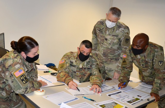 VICENZA, Italy (Aug. 10, 2021) – 414th Contracting Support Brigade Maj. Julio Fernandez, contracting team lead, second from the left, formulates a plan of action during the evaluation exercise held on Caserma Ederle Aug. 10. The Army Contracting Command event, supported by the Mission and Installation Contracting Command headquartered at Joint Base San Antonio-Fort Sam Houston, Texas, in coordination with the 409th CSB from Germany, helps prepare the brigade for potential deployment anywhere in the world.