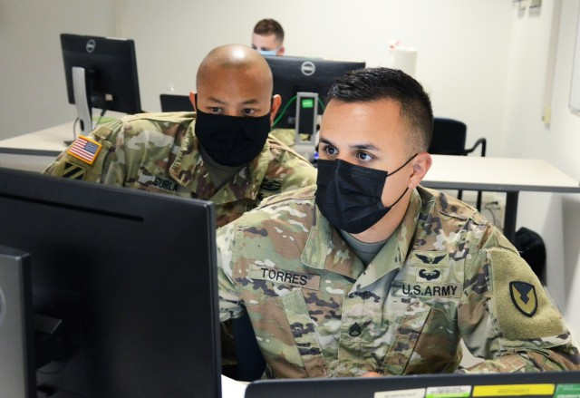 VICENZA, Italy (Aug. 10, 2021) – 414th Contracting Support Brigade Sgt. First Class Justino Surla, left, and Staff Sgt. Luis Torres go over a contracting action during the evaluation exercise Aug. 10. The 414th CSB EXEVAL is the first evaluation the command conducted live since COVID-19 started.