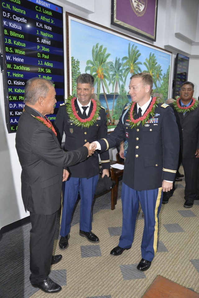 Republic of the Marshall Islands President David Kabua, left, greets outgoing USAG-KA Director of Host Nation Activities Lt. Col. Daniel Young, center, and incoming director Maj. Jay Parsons following the opening day of the Nitijela on Majuro Aug. 9, 2021.
