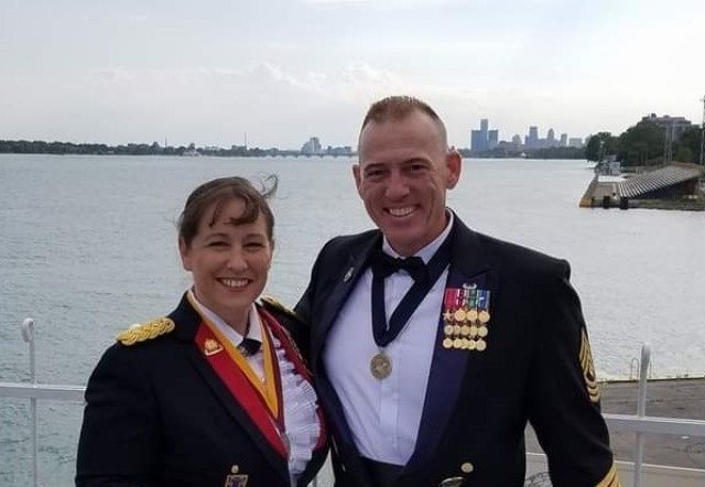 Lt. Col. Jennifer Rader, G3, 1st Theater Sustainment Command, and her husband, Sgt. Maj. Alan Rader, S1 senior noncommissioned officer, 1st TSC, stand near the Detroit River with the Detroit cityscape in the background in 2018.
