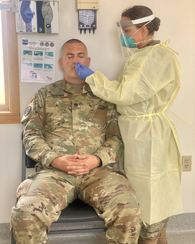 Capt. Elizabeth Babcock, Blanchfield Army Community Hospital medical laboratory manager, demonstrates how to perform a COVID-19 swab on Staff Sgt. Sean Edaburn, 7404th Troop Medical Command non-commissioned officer in charge, at the Fort McCoy Soldier Readiness Processing Site June 24. Medical and dental teams from Blanchfield spent six weeks at Fort McCoy, Wisconsin this summer supporting the level III mobilization exercise Pershing Strike '21. Blanchfield's responsibilities included privileging Reserve component health care providers, training and granting access to electronic health records, and training and certifying qualified personnel on COVID-19 swabbing and shipping requirements. U.S. Army photo by Sgt. 1st Class Jamie Hendzel.