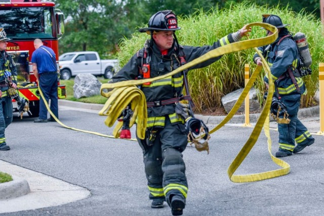Joint Base Myer-Henderson Hall firefighter Jeffrey Lee unrolls a fire hose during the JBM-HH exercise Aug. 4.