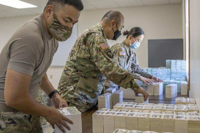 From left to right, Capt. Cynjun Salinas, Lt. Col. Luke Ahn and Spc. Saralin Moon, 326th Financial Management Support Center Soldiers, stack simulated currency after moving their operation in less than two hours during Diamond Saber at Fort McCoy, Wisconsin, Aug. 14, 2021. Diamond Saber is a U.S. Army Reserve-led exercise that incorporates participation from all components and joint services, and it prepares finance and comptroller Soldiers on the warfighting functions of funding the force, payment support, disbursing operations, accounting, fiscal stewardship, auditability and data analytics. (U.S. Army photo by Mark R. W. Orders-Woempner)