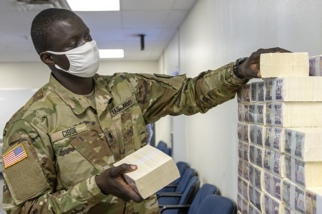 Cadet Serigne Cisse, 374th Financial Management Support Unit officer candidate, stacks play currency for Diamond Saber at Fort McCoy, Wisconsin, Aug. 14, 2021. Diamond Saber is a U.S. Army Reserve-led exercise that incorporates participation from all components and joint services, and it prepares finance and comptroller Soldiers on the warfighting functions of funding the force, payment support, disbursing operations, accounting, fiscal stewardship, auditability and data analytics. (U.S. Army photo by Mark R. W. Orders-Woempner)