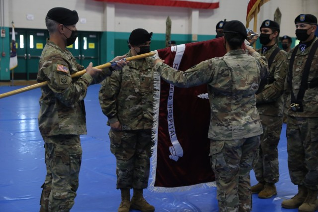 Soldiers assigned to the 14th Field Hospital uncase their unit's colors during the activation and assumption to command ceremony to activate the 14th FH held at Newman Gym on Fort Stewart, Georgia, Aug 17. The 14th FH mission is to provide hospitalization and out-patient services for all classes of patients within the theater in support of the 16th Hospital Center, 44th Medical Brigade, 18th Airborne Corps, Unified Land Operations and the Defense Support of Civil Authorities.