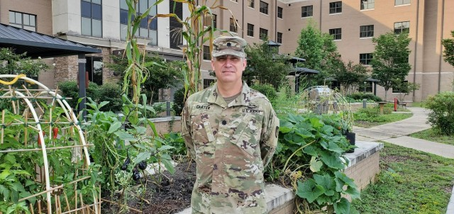 Lt. Col. Jason Carter, a Soldier assigned to the Fort Benning Soldier Recovery Unit, Georgia, posed for a photo in front of the Fort Benning SRU garden where Soldiers grow vegetables, such as potatoes, beans and zucchini. (Photo courtesy of Chaplain Cheonchong Kim)