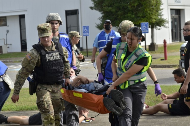 Fort Campbell Military Police and Emergency Medical Services personnel work together to carry a victim to an ambulance following an active shooter scenario Aug. 17 at Building 6563, which was conducted as part of a two-day full-scale exercise.