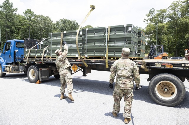 Spc. Ederick Felicianomaldonado (left) and Spc. Baldy Fonrodonaaubert (right) use trailer winch straps to secure munitions to the flatbed trailer prior to transport.