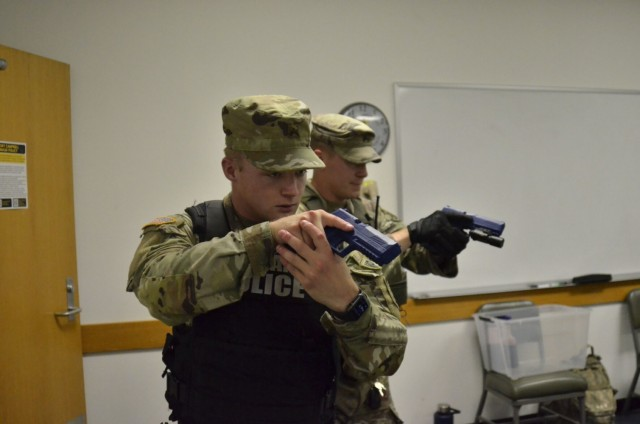 Corporal Kyle Crotty, 561st Military Police Company, 716th Military Police Battalion, left; and Sgt. Jason Wright, collision investigator, Installation Provost Marshal Office, secure a room at Building 6563 Aug. 17 during an active shooter scenario, which was conducted as part of a two-day full-scale exercise.