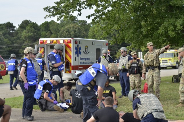 Fort Campbell Military Police and Emergency Medical Services personnel coordinate to make sure victims receive critical care following an active shooter scenario Aug. 17 at Building 6563, which was conducted as part of a two-day full-scale exercise.