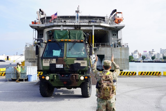 Spc. Eduardo Marin, a signal support systems specialist, assigned to Bravo Battery, 1-1 Air Defense Artillery Battalion, ground-guides a mobile command center, backward onto the United States Naval Ship Guam (T-HST 1) June 26 at Naha Military Port. The port operations are in preparation for movement onto Camp Amami for Orient Shield-21.