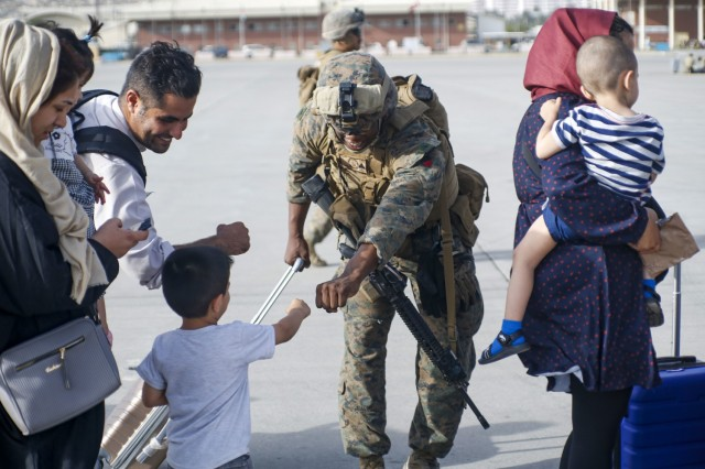 210818-M-JM820-1182 HAMID KARZAI INTERNATIONAL AIRPORT, Afghanistan (August 18, 2021) – A U.S. Marine assigned to 24th Marine Expeditionary Unit fists bumps a child evacuee during a military drawdown at Hamid Karzai International Airport, Afghanistan, Aug. 18. U.S. service members are assisting the Department of State with an orderly drawdown of designated personnel in Afghanistan. (U.S. Marine Corps photo by Lance Cpl. Nicholas Guevara)