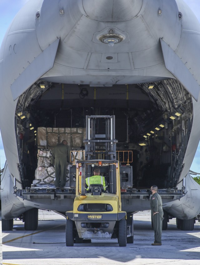 A C-17 Globemaster aircrew assists a member of the Kwajalein airfield team in a cargo loading operation Aug. 14, 2021 at Bucholz Army Airfield on U.S. Army Garrison-Kwajalein Atoll.