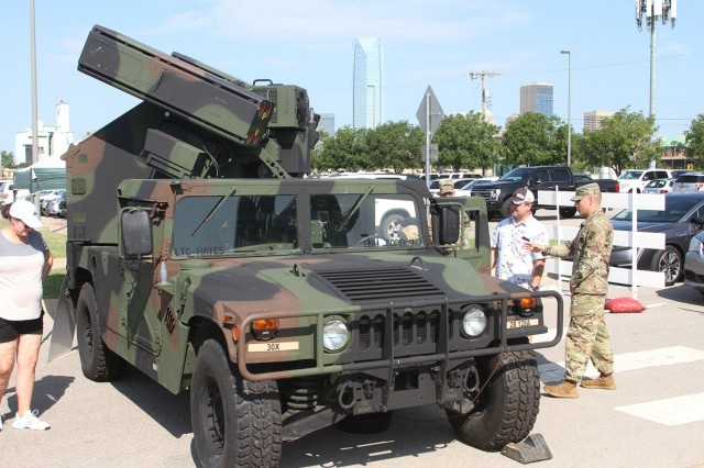 Staff Sgt. Zeke Sandoval, a 2nd Battalion, 6th Air Defense Artillery instructor, tells a father about the Avenger Air Defense System while the man's sons get a closer look during the  USO Experience Aug. 22.