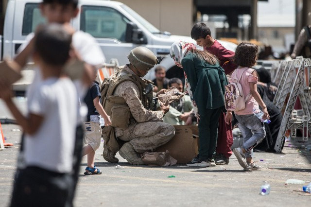 A Marine with Special Purpose Marine Air-Ground Task Force-Crisis Response-Central Command (SPMAGTF-CR-CC) provides meals ready-to-eat to a child during an evacuation at Hamid Karzai International Airport, Kabul, Afghanistan, Aug. 21. U.S. service members are assisting the Department of State with an orderly drawdown of designated personnel in Afghanistan.