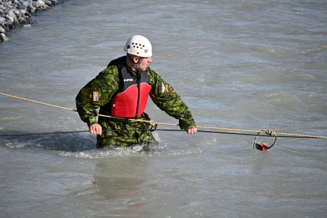 Brig. Gen. Louis Lapointe, deputy commanding general of U.S. Army Alaska, crosses Phelan Creek in Central Alaska on August 18 while observing the final day of training for the students of the Basic Military Mountaineering Course conducted at the Black Rapids Training Site of the Northern Warfare Training Center. The source of the creek is Gulkana Glacier, and the water temperature was approximately 38 degrees Fahrenheit. (Photo by Eve Baker, Fort Wainwright Public Affairs Office)