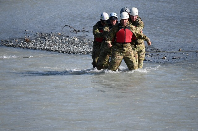 A group of leaders from U.S. Army Alaska practices an un-roped river crossing technique in Phelan Creek in central Alaska. The creek's source is Gulkana Glacier in the Alaska Range, and the water temperature on the day of the crossing was approximately 38 degrees Fahrenheit. (Photo by Eve Baker, Fort Wainwright Public Affairs Office)
