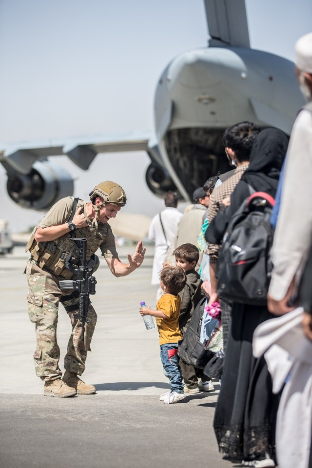 A Marine with Special Purpose Marine Air-Ground Task Force-Crisis Response-Central Command (SPMAGTF-CR-CC) gives a child a fist bump during an evacuation at Hamid Karzai International Airport, Kabul, Afghanistan, Aug. 24. U.S. service members are assisting the Department of State with an orderly drawdown of designated personnel in Afghanistan. (U.S. Marine Corps photo by Sgt. Samuel Ruiz).
