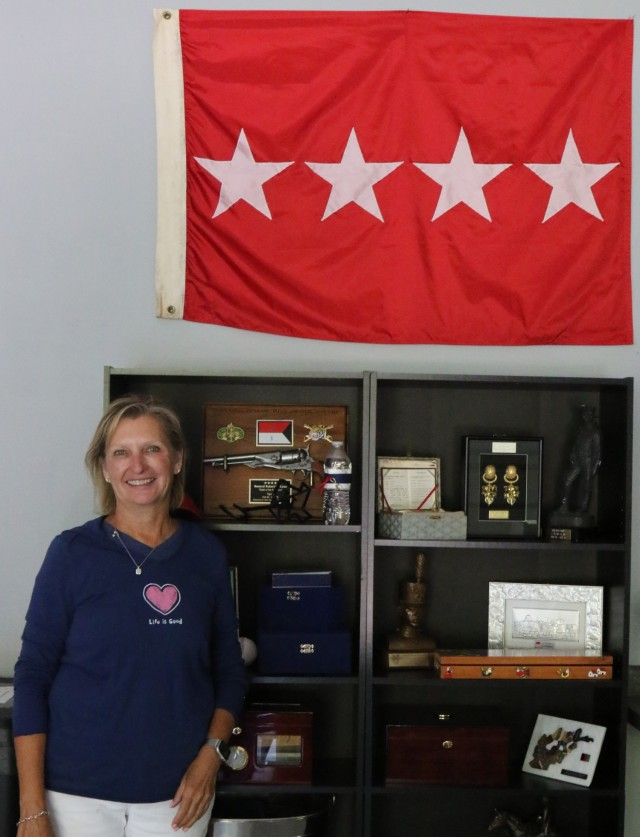Mrs. Jill Cone in front of a bookshelf with some of her late husband's memorabilia. (U.S. Army photograph by Sgt. Bradley Parrish, 11th ACR Public Affairs Office).