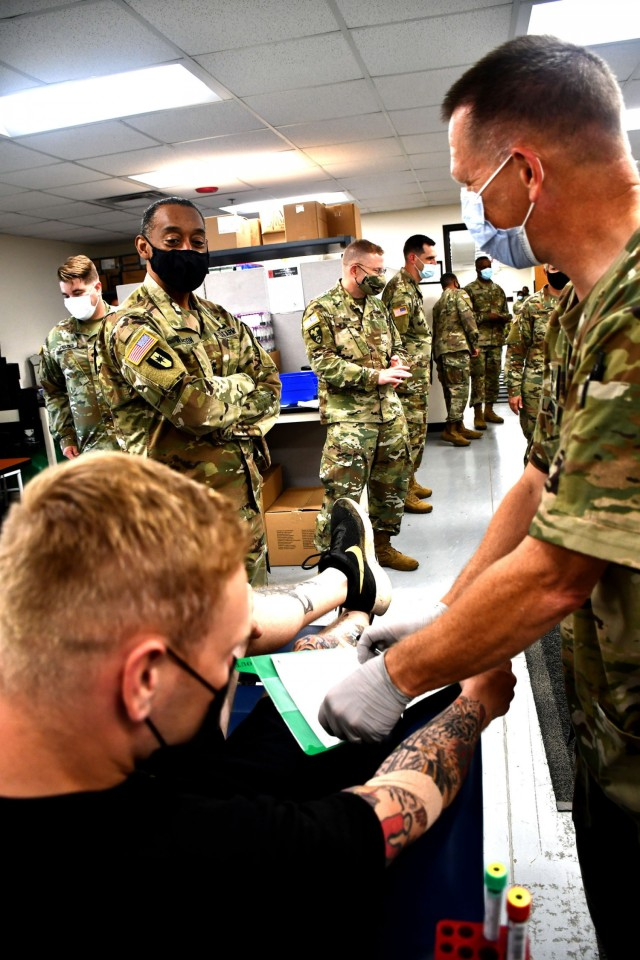 Maj. Gen. Jonathan Woodson, commanding general, Army Reserve Medical Command, observes a blood draw while touring the Soldier Readiness Processing site for the 2021 Cadet Summer Training on Monday, July 12. The SRP site is a part of the ARMEDCOM medical support offered annually to the Fort Knox, Ky. training exercise, and ensures cadets are medically safe to train in the exercise and ready for commissioning. CST is the largest annual training exercise executed by the U.S. Army, graduating almost 10,000 Cadets from Advanced Camp or Basic Camp each summer. More than 250 ARMEDCOM Soldiers have provided support to the exercise, including medics, physicians, x-ray technicians, pharmacy technicians and lab technicians.