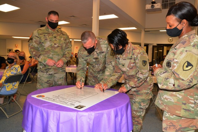 Maj. Gen. Mark T. Simerly, CASCOM and Fort Lee commanding general, and Col. Karin L. Watson, Fort Lee garrison commander, sign the Suicide Awareness and Prevention Month pledge during an observance kickoff breakfast Aug. 26 at the Memorial Chapel Family Life Center. Flanking the senior leaders are Command Sgt. Maj. Jorge C. Escobedo and CSM Tamisha A. Love, the top enlisted leaders for the respective organizations. (U.S. Army photo by Patrick Buffett)