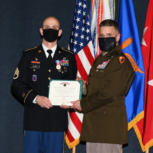 U.S. Army Staff Sgt. Travis M. Adams, who serves as a flight medic with Fort Rucker's air ambulance detachment, receives the Soldier's Medal from Maj. Gen. David J. Francis, U.S. Army Aviation Center of Excellence and Fort Rucker commander, for his courageous actions in responding to a multivehicle accident in the local community during a ceremony at the U.S. Army Aviation Museum Aug. 27, 2021. (U.S. Army photo by Kelly Morris)