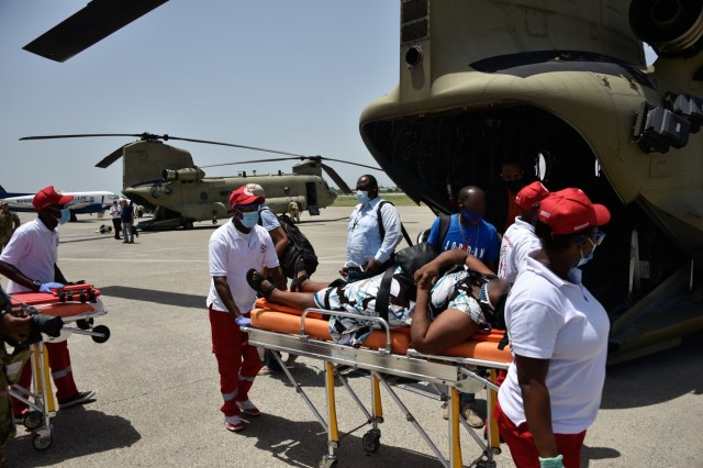 A U.S. Army CH-47 Chinook Helicopter crew and partner rescue agencies transfer a patient following a medical evacuation in Port-au-Prince, Haiti, Aug. 23, 2021. The Coast Guard conducted humanitarian efforts in impacted areas of Haiti following a magnitude 7.2 earthquake, Aug. 14, 2021. (Coast Guard photo by Petty Officer 3rd Class Ryan Estrada)