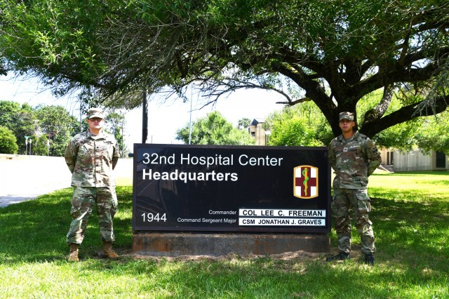 Sgt. Farrell Noel, 115th Field Hospital operating room specialist, (left) and Sgt. Nelson Mercado, 286th Medical Detachment, 32nd Hospital Center, Army practical nursing specialist, stand next to the 32nd Hospital Center Headquarters sign.