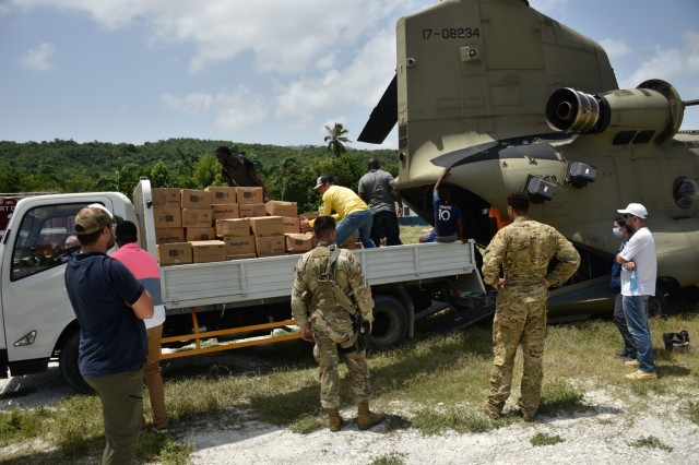 A U.S. Army CH-47 Chinook Helicopter crew and partner agencies deliver emergency medical equipment and food to Haitian citizens in impacted areas of Haiti, Aug. 23, 2021. The Coast Guard and partner agencies conducted humanitarian efforts in impacted areas of Haiti following a magnitude 7.2 earthquake, Aug. 14 2021. (Coast Guard photo by Petty Officer 3rd Class Ryan Estrada)