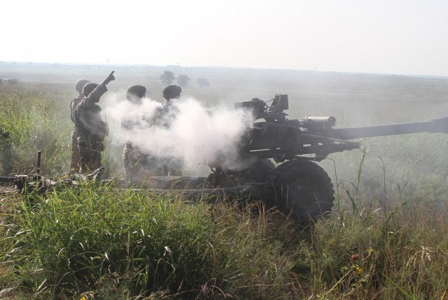 Smoke obscures a B Battery, 2nd Battalion, 2nd Field Artillery gun crew during direct fire training with their M119A3 artillery pieces. Hot temperatures and thick vegetation failed to diminish the enthusiasm of the battalion's Soldiers to practice and perfect their artillery skills.