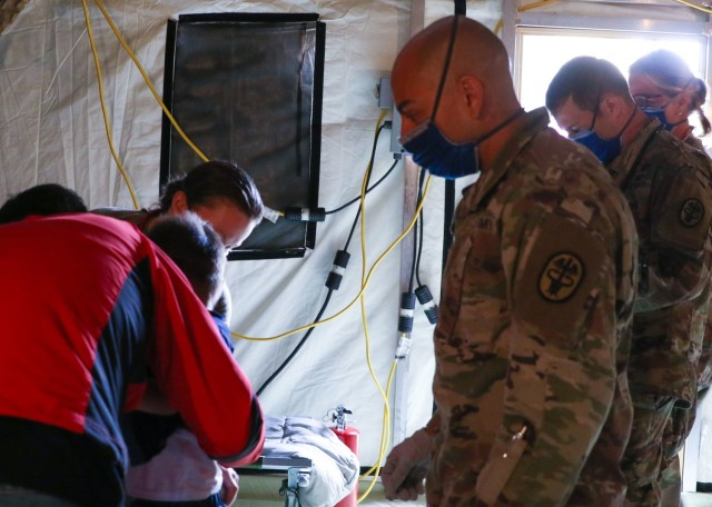 U.S. Army Maj. Jesus Chaves (right), chief nursing officer, U.S. Army Health Clinic Baumholder, Landstuhl Regional Medical Center, evaluates an Afghan evacuee as part of a medical team supporting Operation Allies Refuge at Ramstein Air Base, Aug. 26. The medical team is part of U.S. Armed Forces medical efforts in response to the Afghanistan evacuations at Ramstein Air Base, which has transformed itself into the logistical hub for the evacuation of people from Afghanistan.