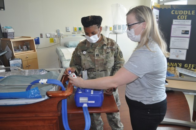 Martin Army Community Hospital Mother-Baby Unit CNOIC Capt. Katherine Basquill-White and Labor and Delivery Unit CNOIC Capt. Decilia Neely assemble the CuddleCot.