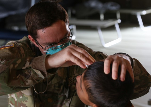 U.S. Army Maj. Philip Goering, a family medicine physician, U.S. Army Health Clinic Wiesbaden, Landstuhl Regional Medical Center, applies medication to an Afghan evacuee seeking medical assistance as part of medical operations in support of Operation Allies Refuge at Ramstein Air Base, Germany, Aug. 26. The medical operations are part of U.S. Armed Forces medical efforts in response to the Afghanistan evacuations at Ramstein Air Base, which has transformed itself into the logistical hub for the evacuation of people from Afghanistan.