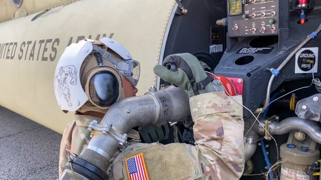 """Soldiers of the 135th Quartermaster Company, 87th Division Sustainment Support Battalion, 3rd Division Sustainment Brigade, 3rd Infantry Division, attach a gas line to a Boeing CH-47 Chinook helicopter during a training event with 2nd Battalion, 3rd General Support Aviation Battalion """"Knighthawks,"""" 3rd Combat Aviation Brigade, on Fort Stewart, Georgia, August 26, 2021. This event was the capstone of a 10-week train up that focused on setting up and manning a forward arming and refueling point. (U.S. Army photo by Spc. Daniel Thompson/50th Public Affairs Detachment)"""