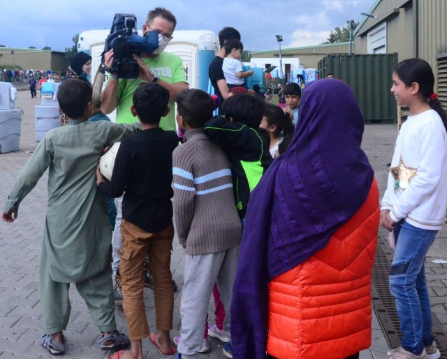 A reporter from Thomson Reuters is mobbed by a group of youngsters wanting to get on camera. (Photo Credit: Shaylee Rawls Borcsani)