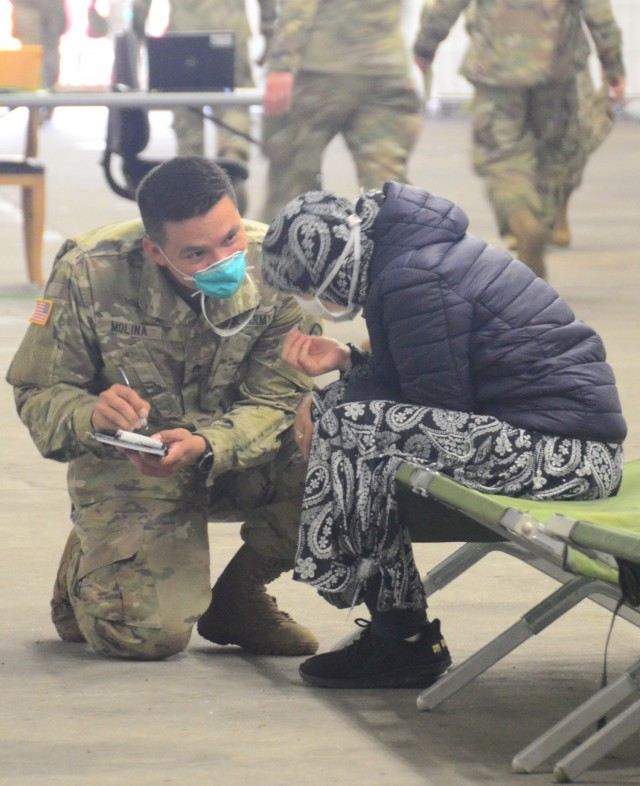 Staff Sgt. Roberto Molina, a Landstuhl Regional Medical Center respiratory technician, takes information from one of the evacuees. (Photo Credit: Shaylee Rawls Borcsani)