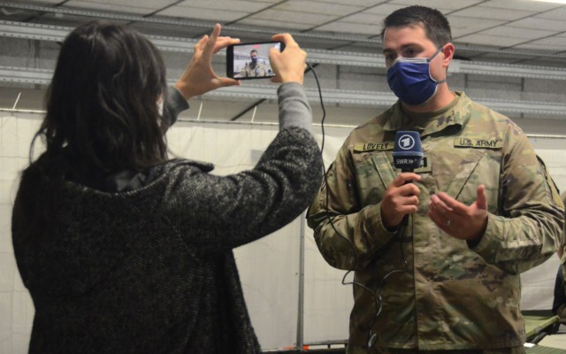 Cpt. Alex Lovely, 16th Sustainment Brigade officer in charge of the evacuee housing area at Rhine Ordnance Barracks explains the shelter, care and feeding of the travelers to a reporter from the German SWR outlet. (Photo Credit: Shaylee Rawls Borcsani)