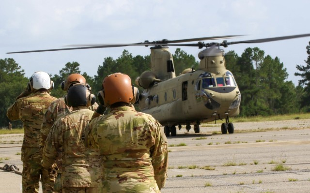 """Soldiers of the 135th Quartermaster Company, 87th Division Sustainment Support Battalion, 3rd Division Sustainment Brigade, 3rd Infantry Division, walk to a Boeing CH-47 Chinook helicopter during a training event with 2nd Battalion, 3rd General Support Aviation Battalion """"Knighthawks,"""" 3rd Combat Aviation Brigade, on Fort Stewart, Georgia, August 26, 2021. This event was the capstone of a 10-week train up that focused on setting up and manning a forward arming and refueling point.(U.S. Army photo by Sgt. Javiera Scott/50th Public Affairs Detachment)"""