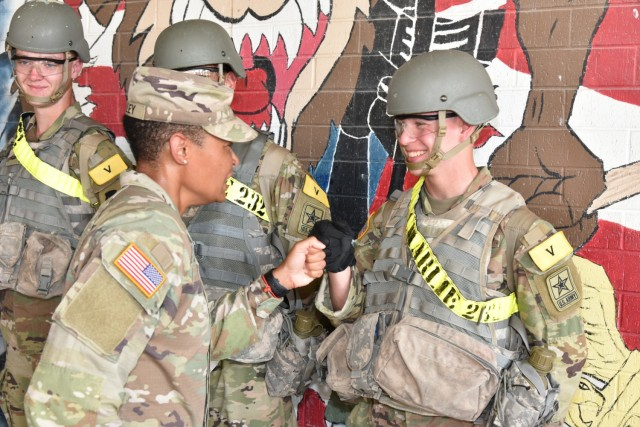 Command Sgt. Maj. Chalawnda M. Kelley, Command Sergeant Major 232nd Medical Battalion, fist bumps Pfc Ryan Jones after he was recognized with a commander's coin.