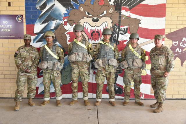 (left to right) Command Sgt. Maj. Deanna Carson, 187th Medical Battalion Command Sergeant Major with Pfc Jalun Taylor, Pfc Blair Sutcliffe, Pfc Jaden King, and Pfc Ryan Jones, from C. Co. 232nd Medical Battalion, with Lt. Col. Dennis Segui, Commander 187th Medical Battalion. LT. Col. Segui presented the four Soldiers with commander's coins to recognize their selfless service in helping a fallen man at the Fort Sam Houston Exchange.