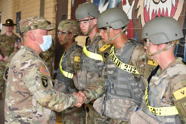 Lt. Col. Dennis Segui, Commander 187th Medical Battalion, shakes hands with Pfc Jaden King after presenting him with a commander's coin.